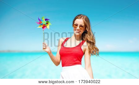 summer holidays, travel, people and vacation concept - happy young woman in sunglasses with pinwheel over blue sky and sea background