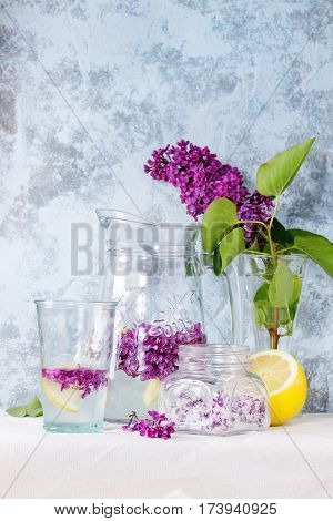Glass jar of lilac flowers in sugar, glass and pitcher of lilac water with lemon, and branch of fresh lilac on white linen tablecloth with blue textured wall at background.