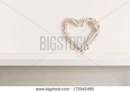 Wicker heart on clean bright white shelving