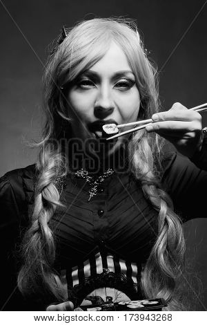 Renaissance gothic girl eating sushi over grey background