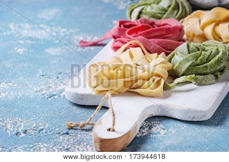 Variety of colored fresh raw uncooked homemade pasta tagliatelle green spinach, pink beetroot and traditional yellow on white wooden cutting board over blue concrete background.