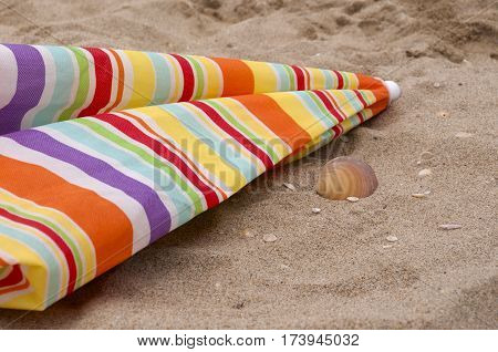 Colored parasol at the sea over the sand