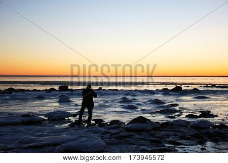 Icy coast with a photographing man silhouette by sunset