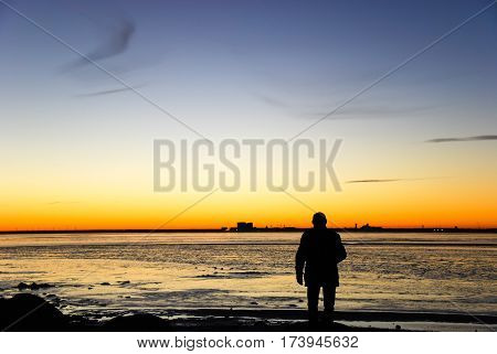 Man silhouette watching the skyline of the swedish city Kalmar in the horizon by sunset