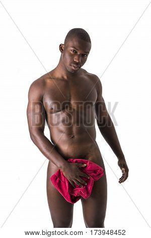 Totally naked young black male bodybuilder hiding genitalia with hands, smiling at camera, isolated on white background