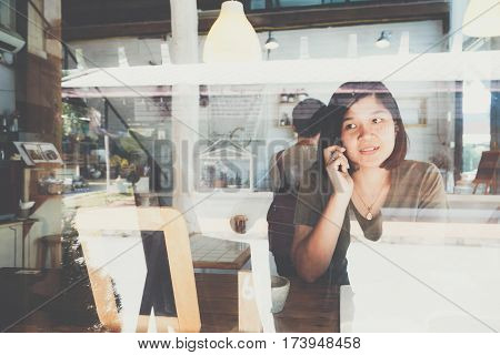 Woman Drinking Coffee In Vintage Cafe And Talking Cellphone