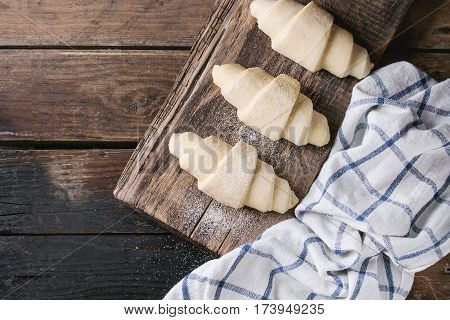 Raw unbaked croissant on wooden chopping board with kitchen towel over old dark wood background. Top view