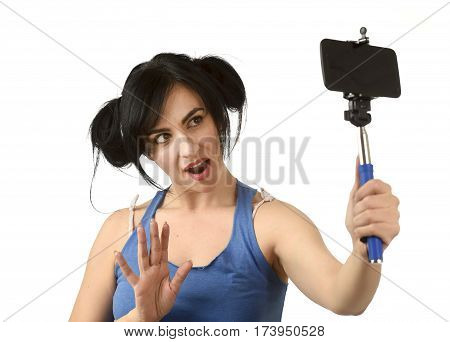 young attractive and sexy woman taking selfie photo with stick and mobile phone camera posing happy and playful isolated on white background in shooting self portrait