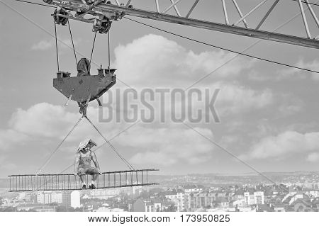 Sunny day at construction. Relaxed vintage builder sitting on crossbar hanging from the crane above the city with a newspaper on his head hiding his face from the sun worker monochrome people concept