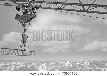 Working high. Muscular confident retro builder standing on a crossbar hanging high above the city copyspace profession fearlessness heights peaceful confident successful development city concept