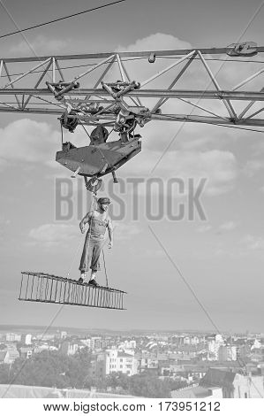 Simple worker. Vertical black and white shot of a strong confident retro handyman overseeing his city working high on a construction site standing on a crossbar dangerous profession vintage concept