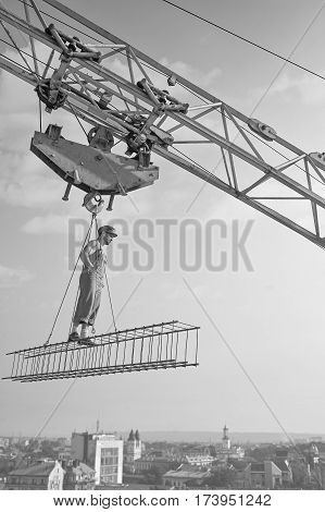 Retro professional. Vertical monochrome shot of a professional builder dressed vintage styled standing on crossbar hooked to construction crane at the site profession job occupation building industry