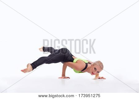 Balance and strength. Beautiful strong female gymnast performing a handstand working out smiling to the camera isolated on white copyspace