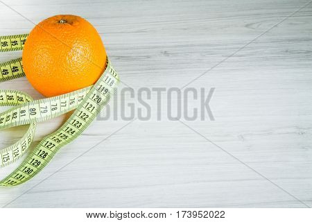 Cm With An Orange On A Wooden Background