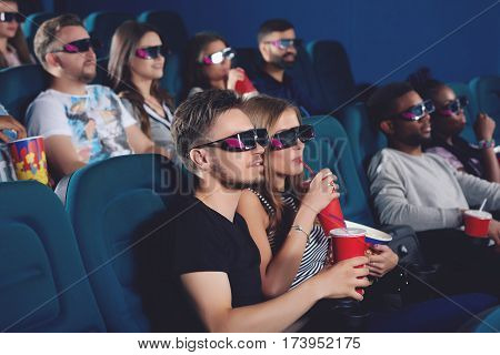 Side view of couple wearing in 3d glasses sitting in modern cinema hall, eating popcorn, drinking cola and looking at projector. Boyfriend and girlfriend watching movie and spending time together.