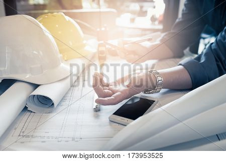 Close up hand of civil engineer people with drawing blueprint discussion in the office