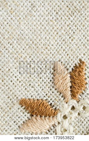Embroidered fragment on flax by cotton threads. Macro embroidery texture flat stitch. Geometric ornament. Needlework.