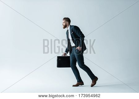 Side view of handsome bearded businessman running with briefcase on grey