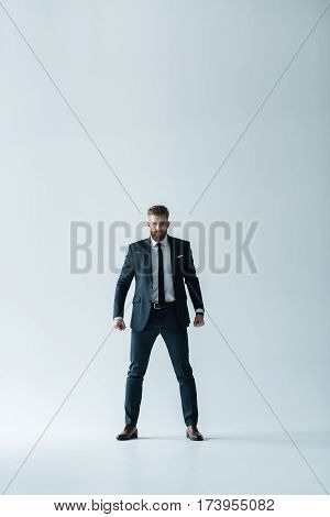 Stylish bearded businessman with clenched fists looking at camera