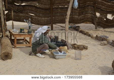 Eastern Desert Egypt - January 24 2013: Eastern Desert Egypt - January 24 2013: Bedouin man preparing food in the desert of Egypt