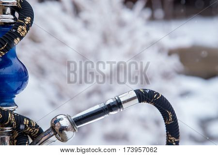 Big Hookah For Tobacco Made Of Metal, Glass And Ceramics. Snowing. Snow Background. White