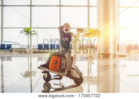 Cute Little Boy With Orange Suitcase At Airport. The Boy On The Trolley And The Airport