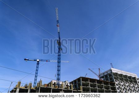 constructionsite with two bulding cranes against blue sky