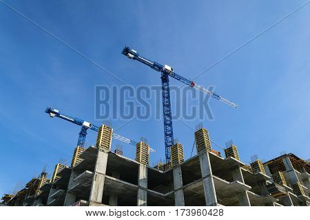 constructionsite with two bulding cranes agenst blue sky
