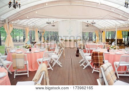Beautifully decorated in peachy colour wedding hall with guests numbered tables and newlyweds table