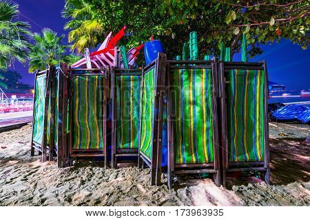 Deck chairs on a beach in Thailand at night
