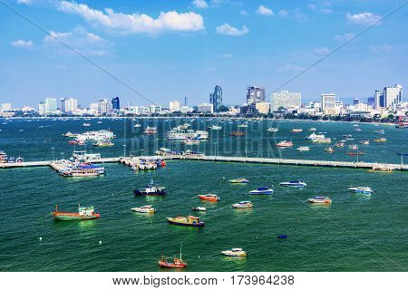 PATTAYA THAILAND - JANUARY 25: This is a view of Pattaya harbor area with boats and pier and city buildings in the distance on January 25 2017 in Pattaya