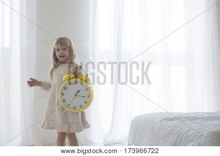Portrait of little adorable girl holding alarm clock, isolated over white
