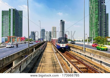 BANGKOK THAILAND - JANUARY 30: BTS Sky train arriving in Saphan Taksin station on Taksin bridge with city buildings and roads on each side on January 30 2017 in Bangkok