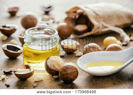 Natural Macadamia Oil And Nuts On Wooden Board. Healthy Product