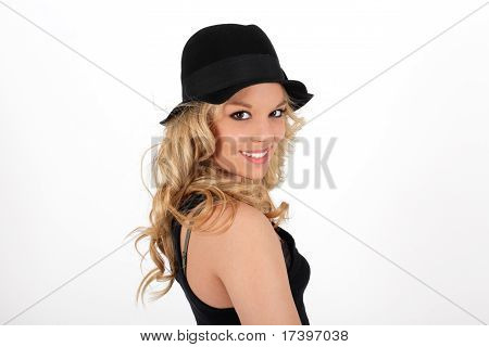 Young blonde teenager smiling girl in studio with black hat