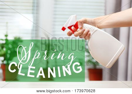 Spring cleaning concept. Male hand with sprayer on window background