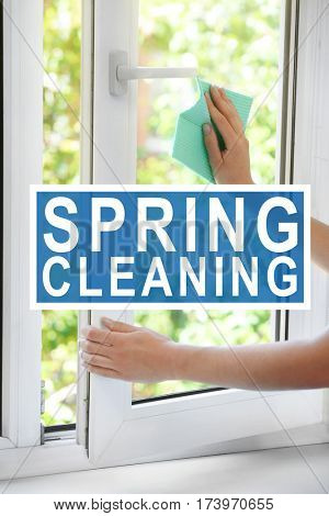 Spring cleaning concept. Female hands washing window at home