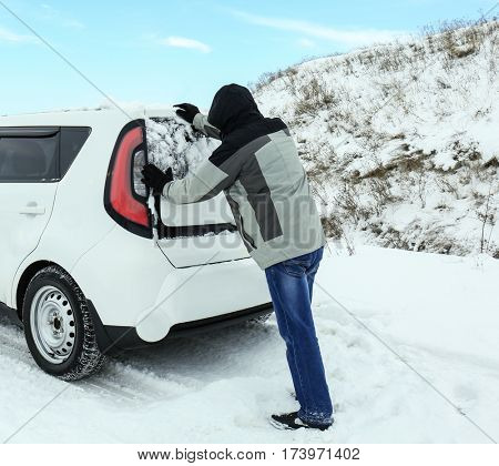 Man pushing car stuck in snowdrift on winter road
