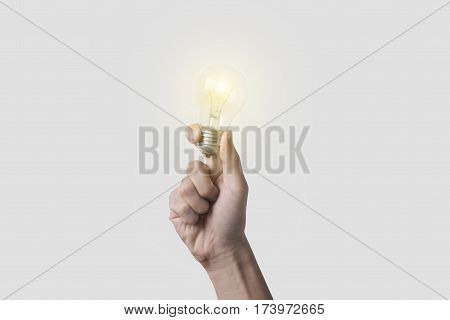 hand holding light bulb on gray background. concept of new ideas with innovation and creativity.