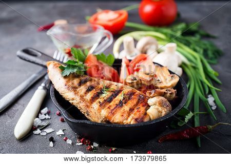 Marinated grilled healthy chicken breasts with fresh herbs and vegetables on a pan on a stone board,
