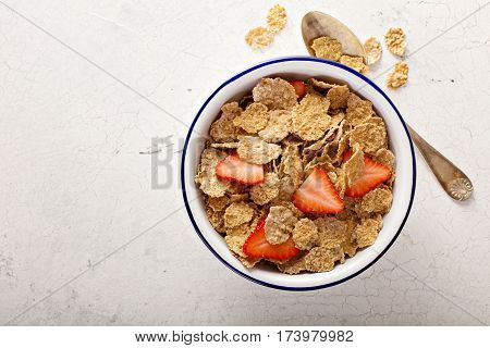 Multigrain wholewheat healthy cereals with fresh berry for breakfast overhead shot with copyspace on white