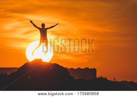 Human silhouette jumping at solar disk sunny summer sunset drive holidays and vacations