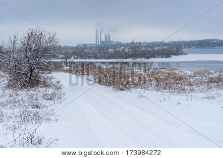 Winter landscape with snow covered earth road near Dnepr city Ukraine