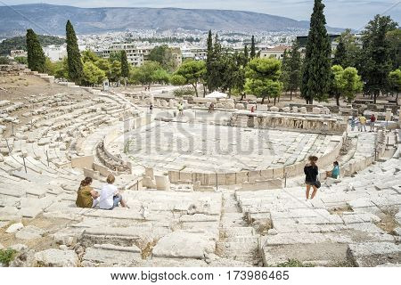 ATHENS, GREECE, SEPTEMBER 6,2016: Tourists walking amonst the remains of The Theatre of Dionysus, built at the foot of the Athenian Acropolis. Dedicated to Dionysus, the god of plays and wine.