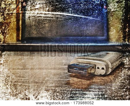 Laptop and flash pen drive arranged on table. Photos in a grunge style.