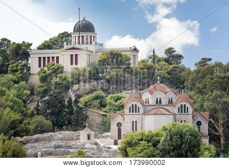 ATHENS, GREECE, SEPTEMBER 7, 2016: Exterior view of The Church Of Agia Marina (down) and National Observatory of Athens (up), Greece.