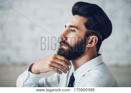 Thinking man making decision. Young handsome bearded man solving the business problem. Perfect skin and hairstyle of elegant male. Toned image with noise