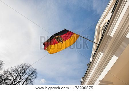 Low angle view of German flag on government building against cloudy sky; Tallinn; Estonia; Europe