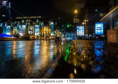 Kiev city by night.  Kiev, Ukraine - May 15, 2014: Empty street in central Kiev Ukraine late at night. Rain and wet asphalt, neon advertising signs on buildings with reflections in the street.