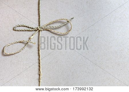 String bow tied over recycled paper, with copy space.